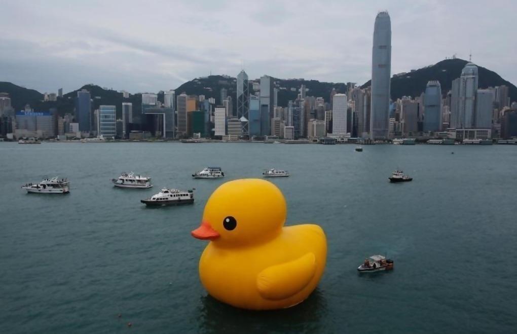 A massive rubber ducky in a city river.