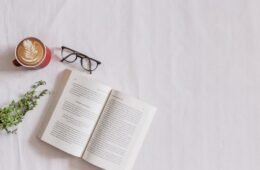 book page beside eyeglasses and coffee